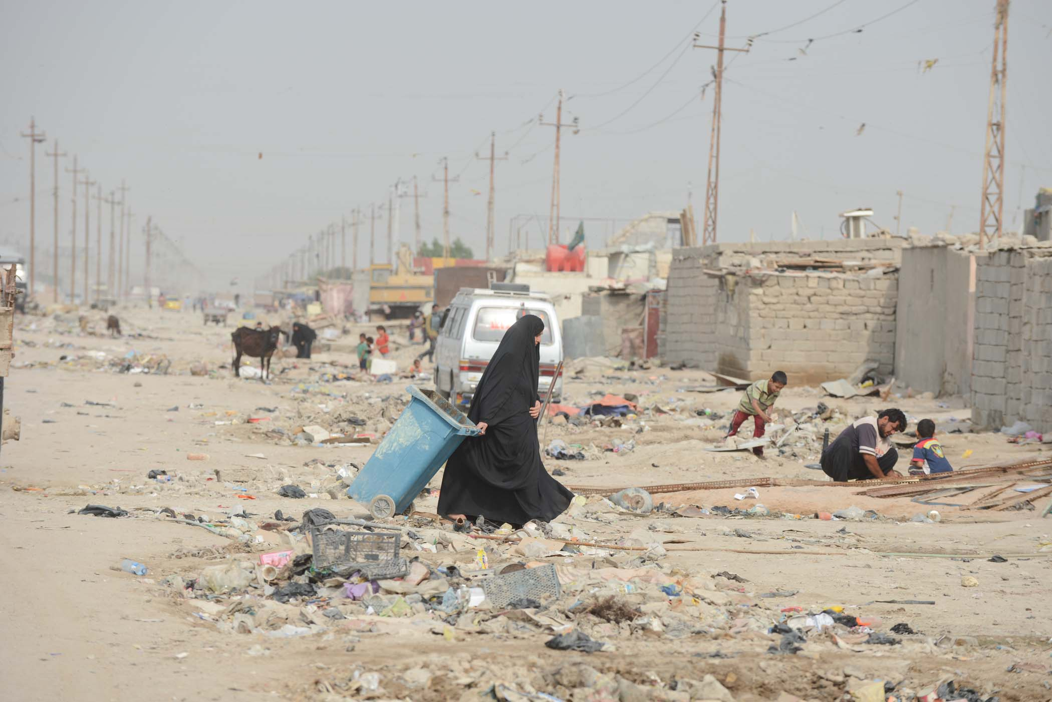 A Woman Drags A Rubbish Bin Across The Litter-filled Streets Close To Basra
