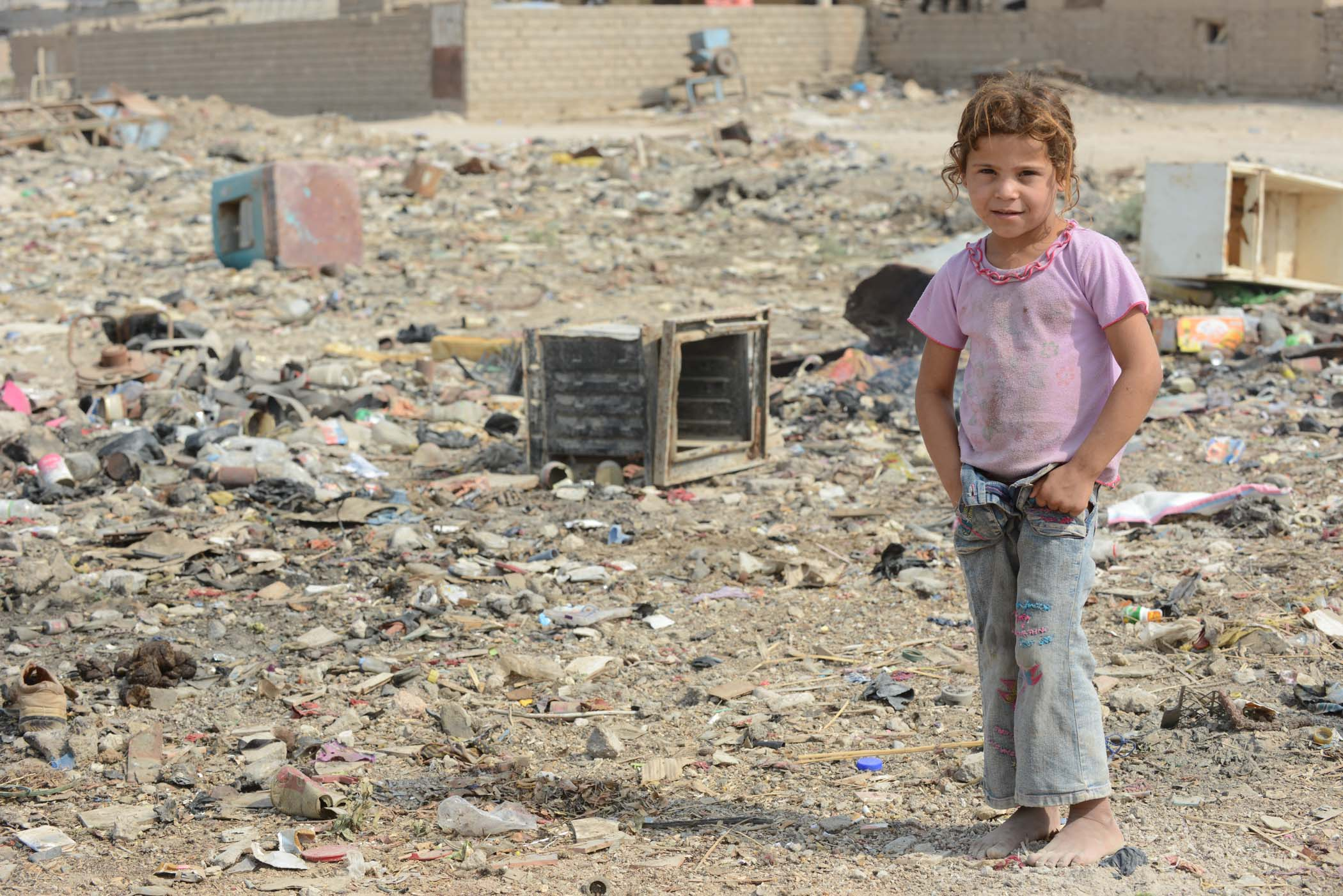 Extreme Poverty. A Young Girl Lives Next To An Overflowing Rubbish Tip Near Basra