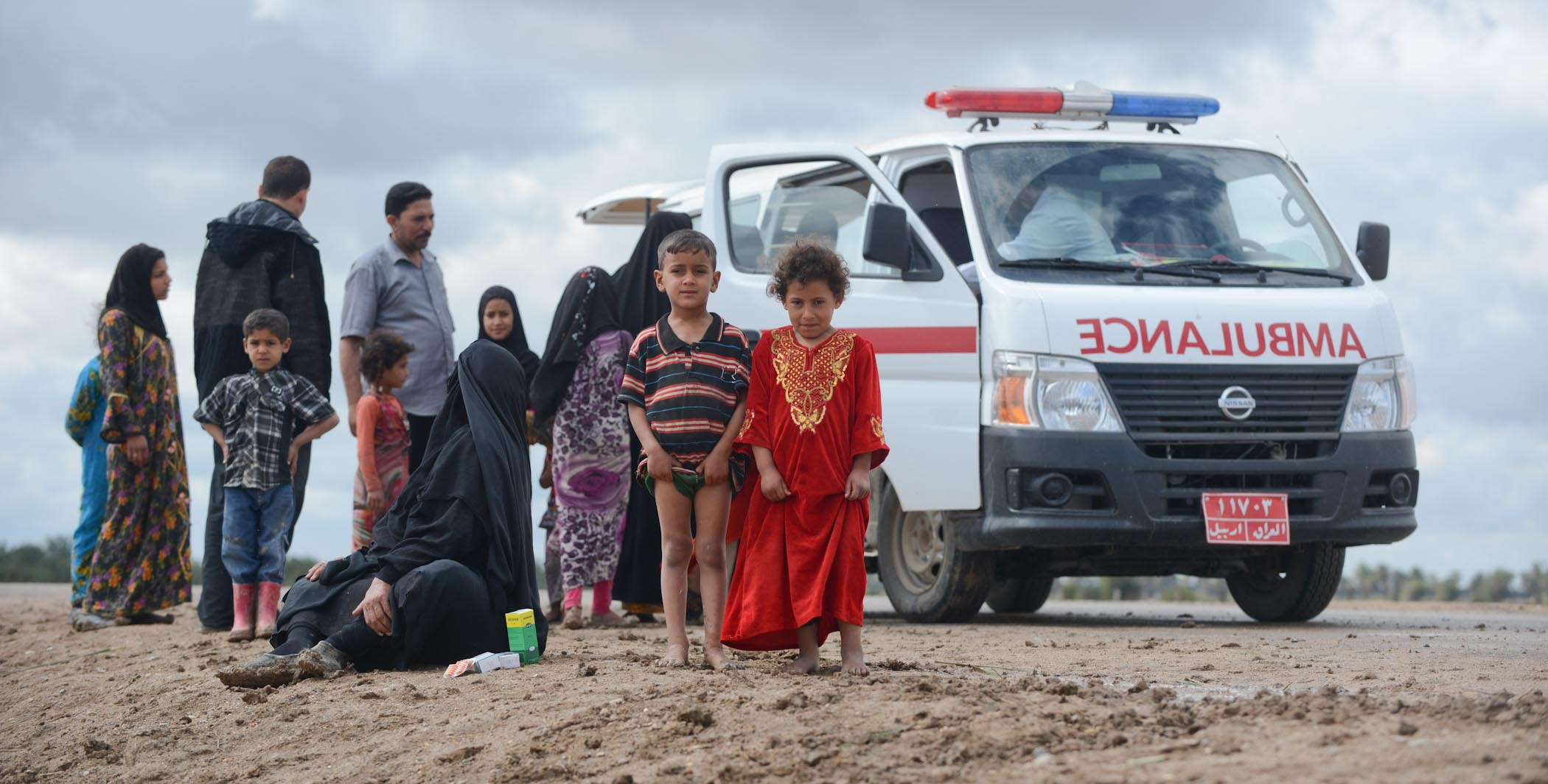 A Brother And Sister Waiting To See Medical Staff On One Of AMAR's Mobile Clinics That Has Just Arrived At Their Remote Village In Southern Iraq