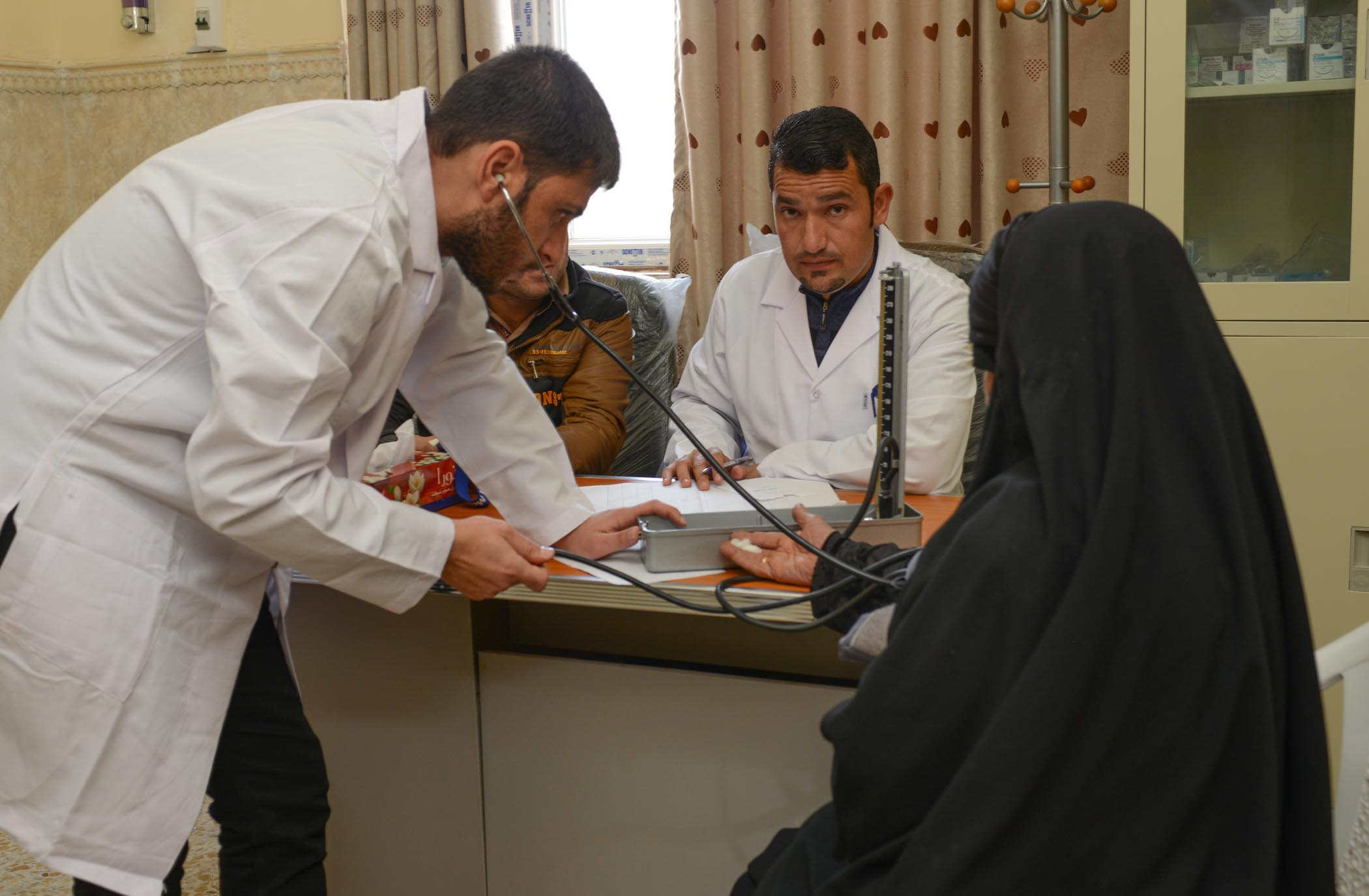 Medical Staff Testing A Women's Blood Pressure At AMAR's Najaf Clinic