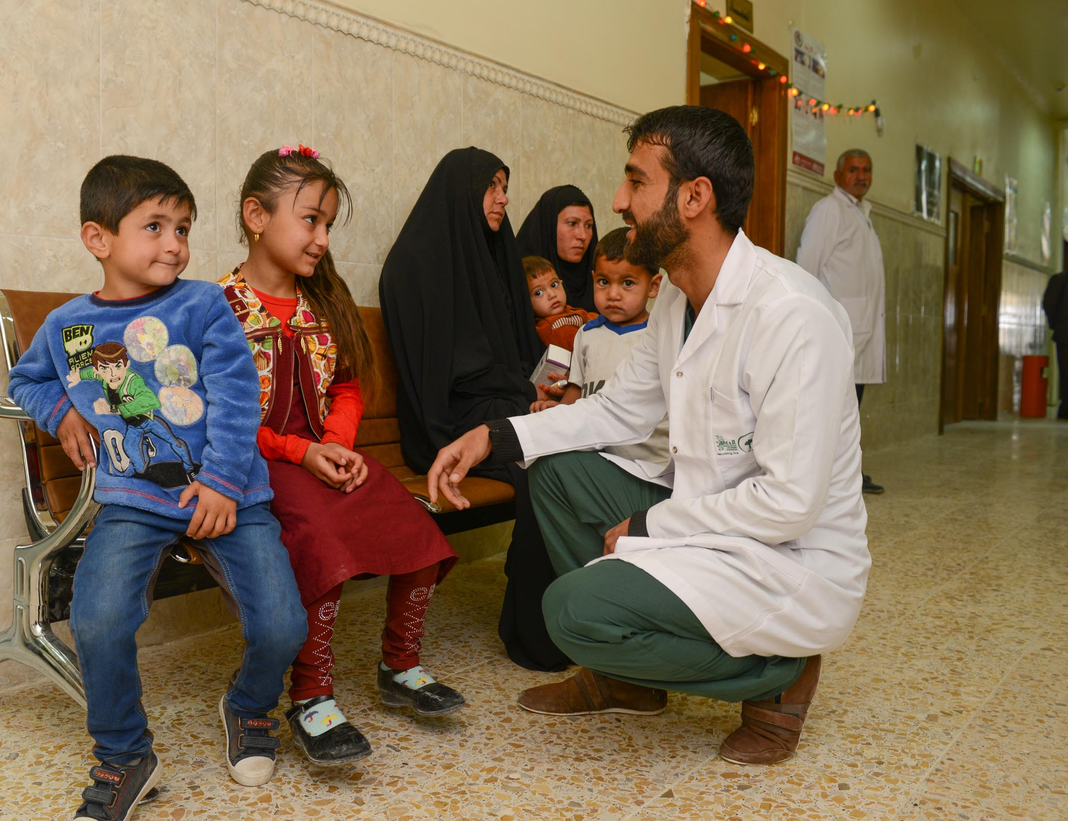 A Doctor Shares A Joke With Refugee Children At AMAR's Najaf Clinic
