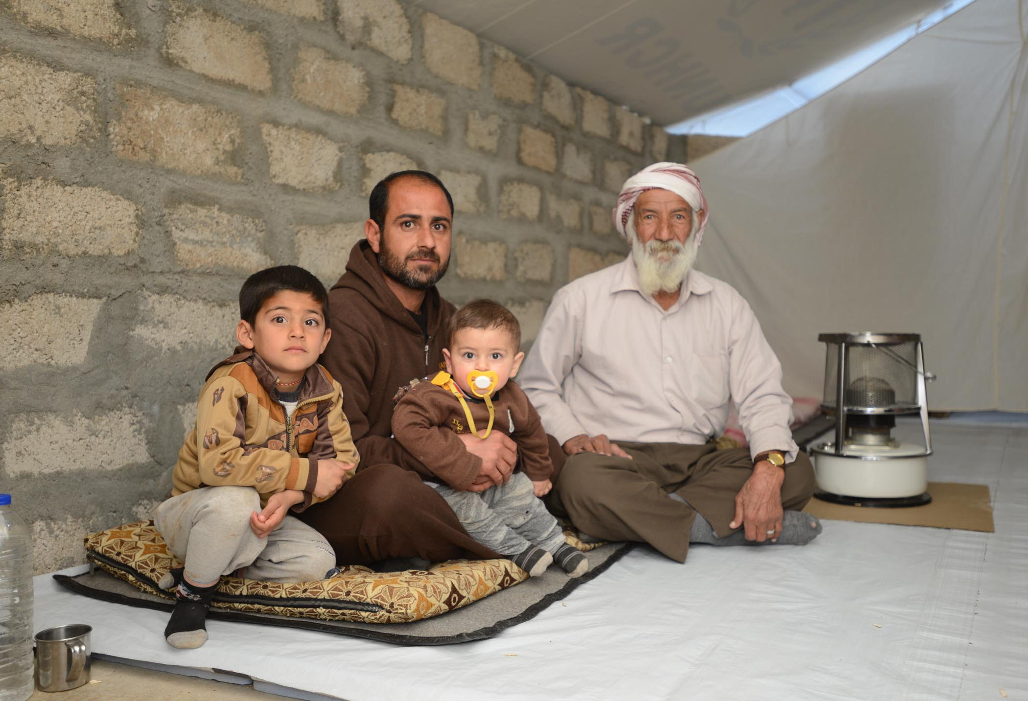 A Yazidi Grandfather, His Son, And Two Grandchildren In Their Spotless Tent In Khanke Camp