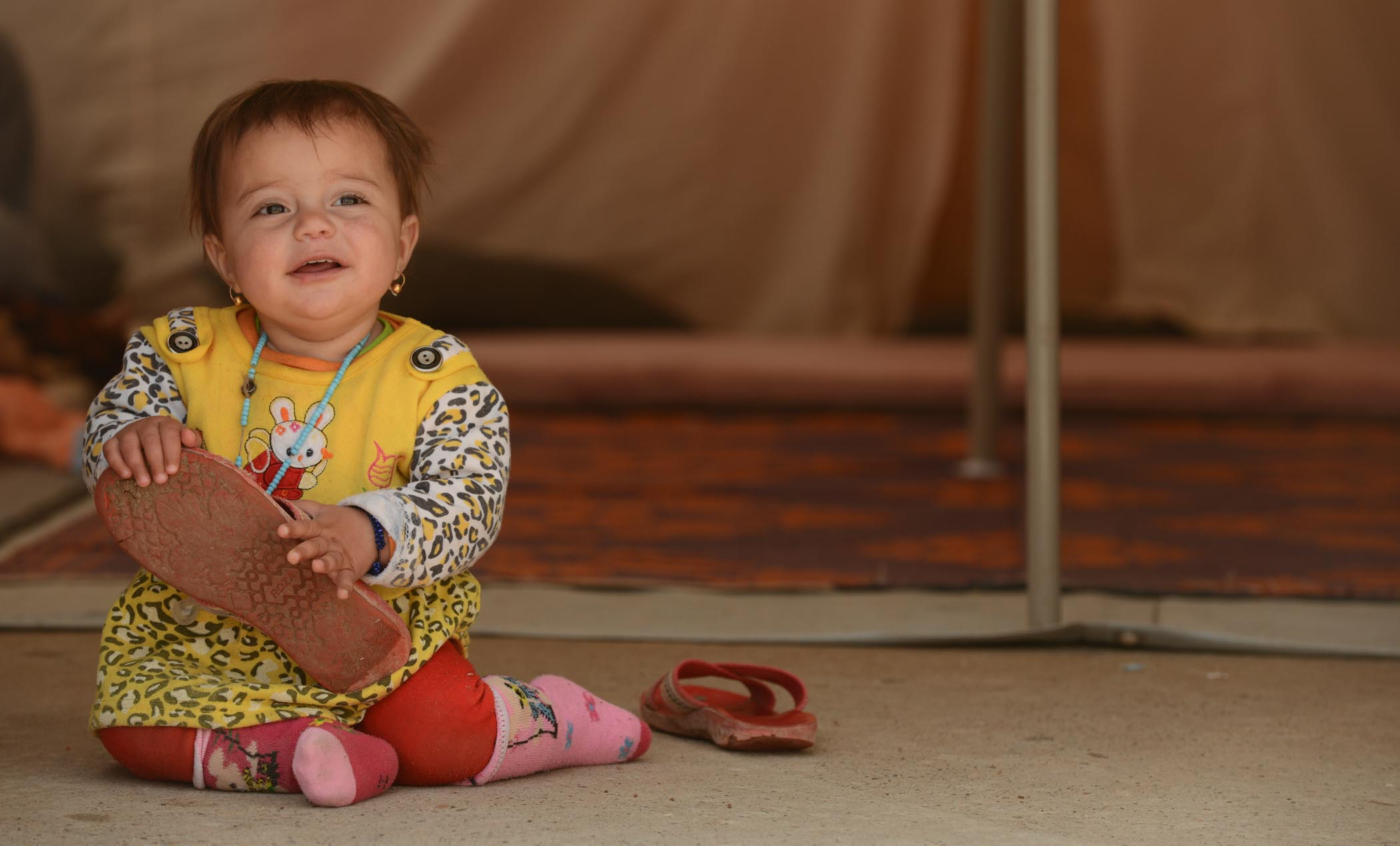A Baby Plays With Her Mum's Shoes In Khanke Camp