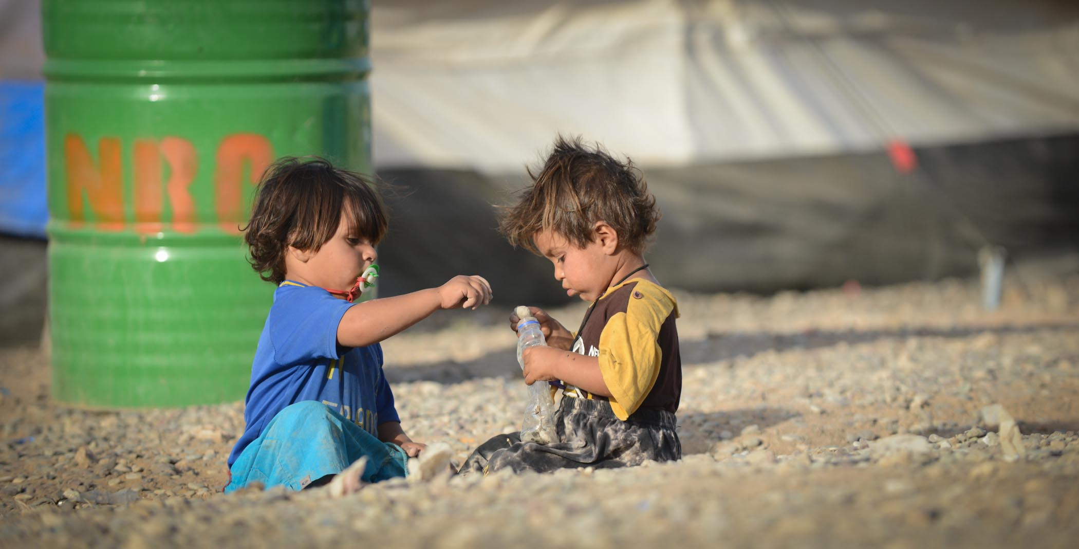 Two Babies Playing With An Old Plastic Bottle In The Baharka Refugee Camp In Erbil