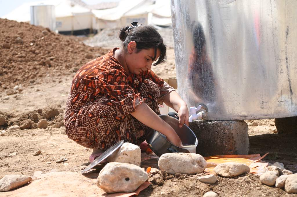 A Young Refugee Washing The Family Dishes Outside Her Tent