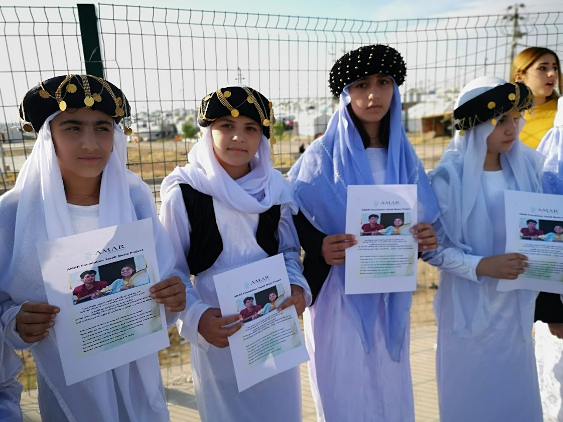 traditionally dressed yazidi girls hold AMAR posters